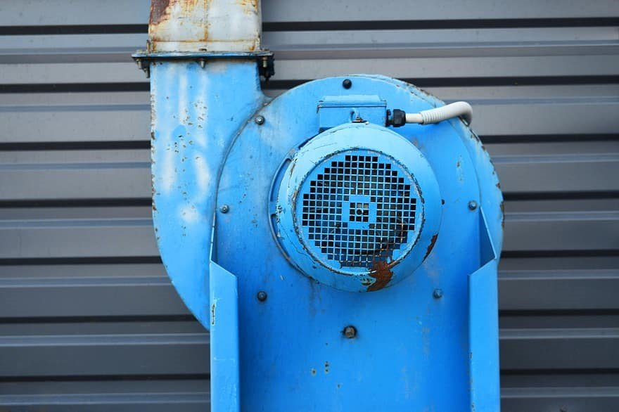 An industrial centrifugal fan connected in a system installation